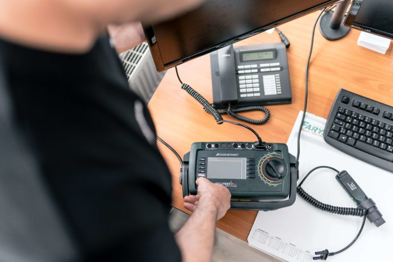 Prüfer beim messen eines elektrischen Betriebsmittels nach DGUV Vorschrift 3 bzw. BGV A3